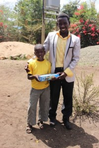 Praygod and his Dad with gift from his sponsors